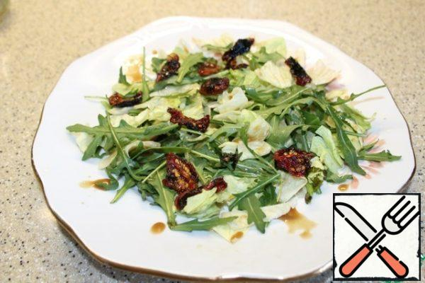 On the dish, put the large torn iceberg lettuce leaves and arugula leaves, dried tomatoes, sprinkle with a small amount of dressing.