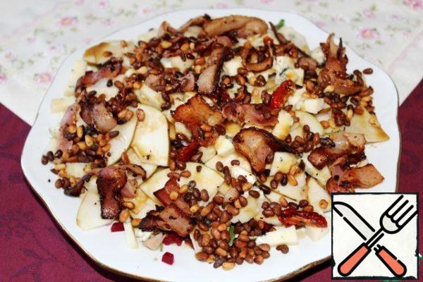Top the salad with nuts and bacon, pour the dressing. I advise you not to use the entire dressing, but to serve the leftovers separately, so that those who wish can add to their taste.
