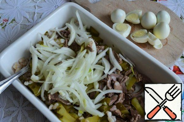 Add the cucumbers and the onion that has been strained from the vinegar. Peel the eggs and cut them into halves.