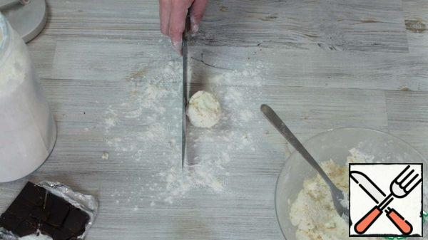 Then we dust the table with flour and shape it. In order to form beautiful and smooth sides of cheesecakes, do the following: put the cheesecake on the table and scroll it, between the knife and the flat part of the blade) and the hand and slightly pressing.