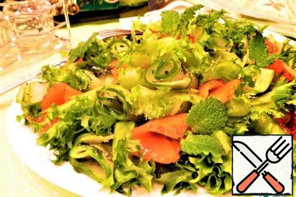 Place the pickles and slices of salted salmon on top of the salad and garnish with small mint leaves.