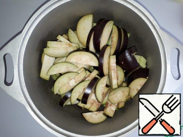 Add the sliced eggplant to the courgettes in the cauldron.