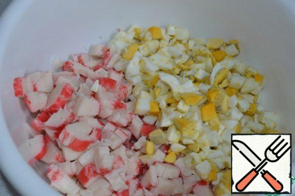 Cut the crab sticks and boiled eggs into cubes and put them in a salad bowl.