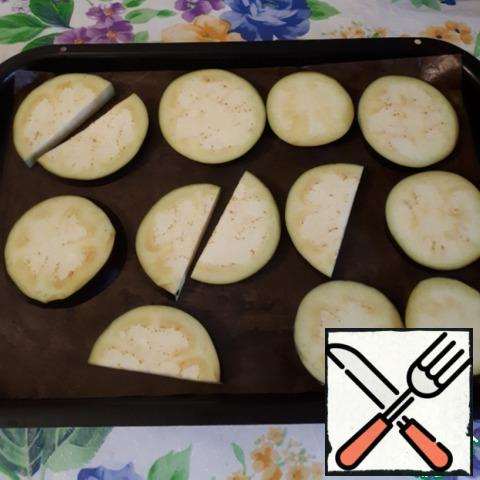 Cut the eggplant into 1 cm thick circles and bake in the oven.