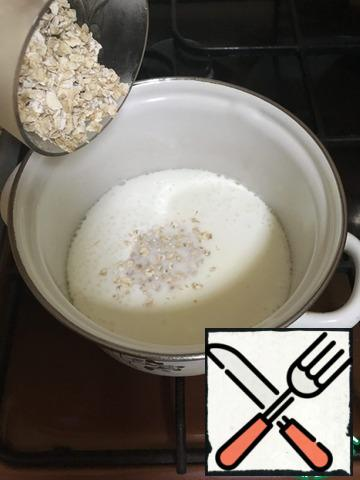 Bring the milk to a boil, stir in the oat flakes and cook over low heat until ready. Remove the ready porridge from the fire and let it stand for about 10 minutes.
