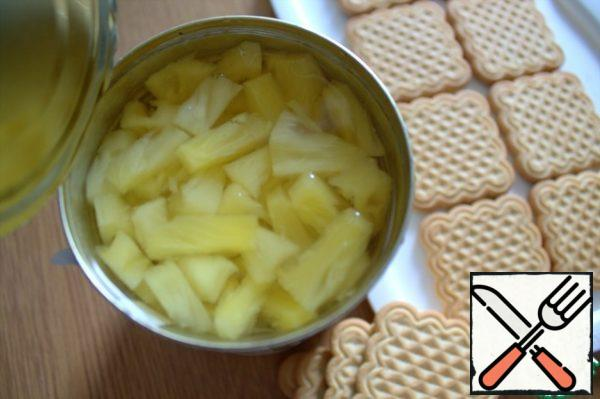 Use a jar of pineapples in syrup. If you have pineapples in circles, you can put them on the bottom instead of cookies, and crumble the cookies into the base.