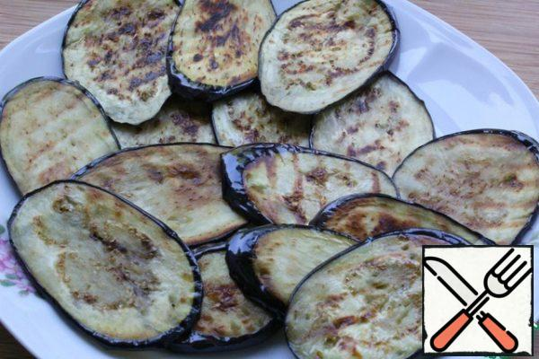 Fry on both sides in vegetable oil, smear with squeezed garlic. I fried the grill in a pan, smearing the eggplants on both sides with vegetable oil.