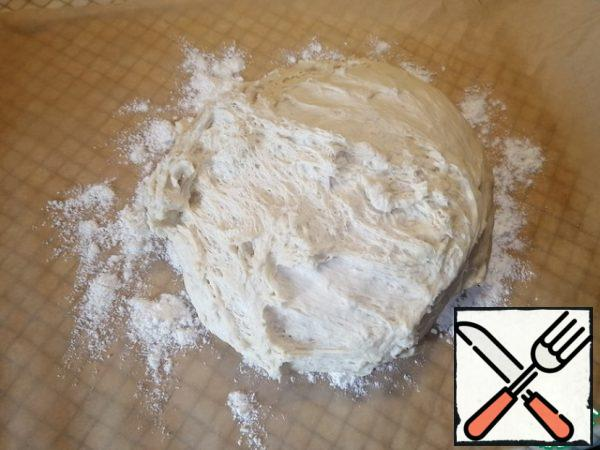 Cut off a large piece of parchment paper to cover the entire baking sheet. Sprinkle the surface with flour and knead our dough for 10 minutes.