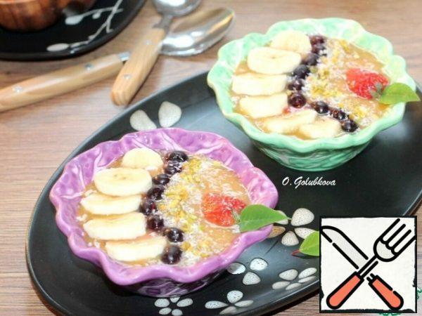Pour the fruit puree into the bowls. Garnish the smoothie with berries, fruit, coconut shavings, nuts, and a mint leaf.