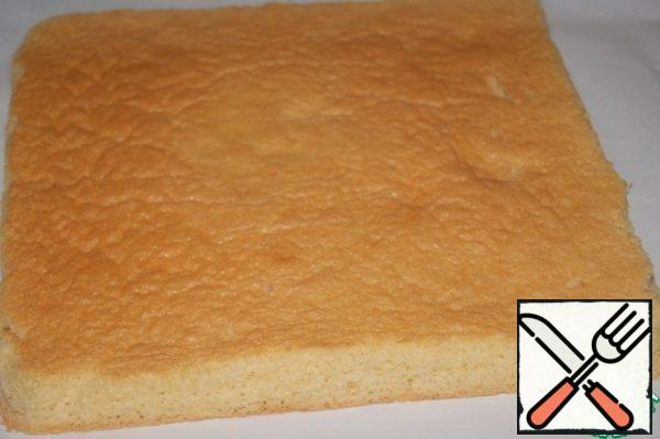 """Remove the cooled biscuit from the paper on which it was baked and place it on a clean sheet of paper with the """"sunburned"""" side up. Cover with a napkin and prepare a cream that will be applied to the """"tanned"""" side."""