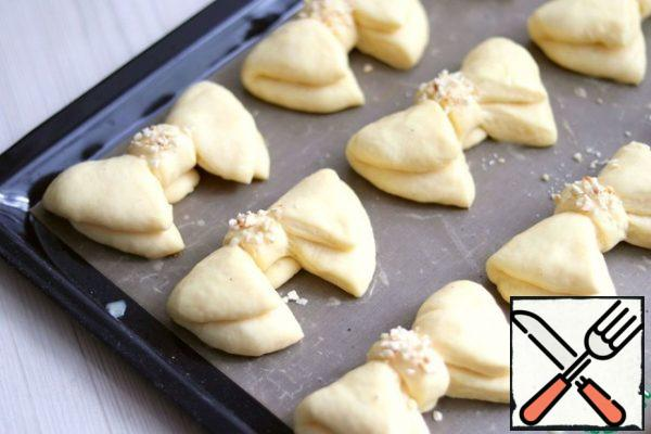 Put the formed buns-bows on a silicone baking Mat or parchment and put on a proofing (10-15 min.). then grease with beaten egg. Sprinkle the middle with fried and crushed almonds. Send the rolls to the oven preheated to 190C and bake until Golden.