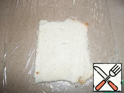 Cut the crusts off the slices of bread. Cut off the food wrap of the appropriate size so that you can wrap the roll. Put a slice of bread on the film, roll out a little with a rolling pin, not too thin. This operation will allow you to compact the structure of the bread.