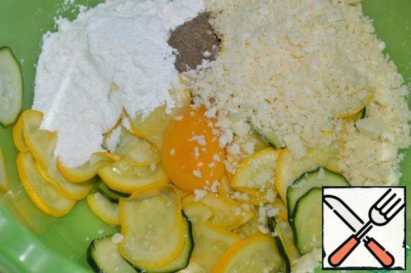 Pour the flour, grated Parmesan, and ground pepper into a bowl with the zucchini. Add egg.
