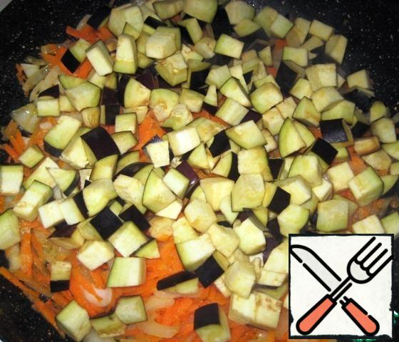 Heat the vegetable oil in a frying pan and send the onion and carrot to fry on medium heat for 3-4 minutes, do not forget to stir. Add the eggplant to the pan. Continue to fry for another 4-5 minutes, constantly stirring the vegetables.