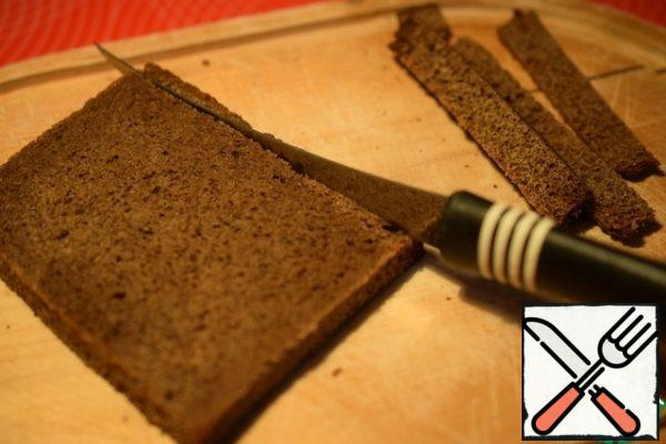 Cut off the crusts from slices of black bread.
