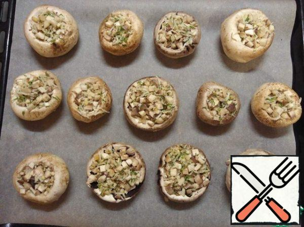 Put the mushrooms on a baking sheet. Top with a little grated cheese on a small grater.