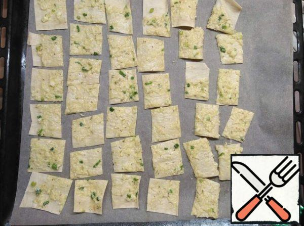 Cut the smeared pita bread into strips with food scissors, then into squares or triangles.