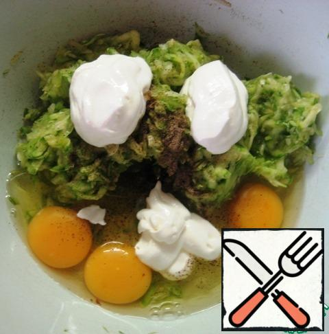 Add to them eggs, sour cream, a pinch of salt and black pepper. Mix thoroughly. Add flour and baking powder. Stir.