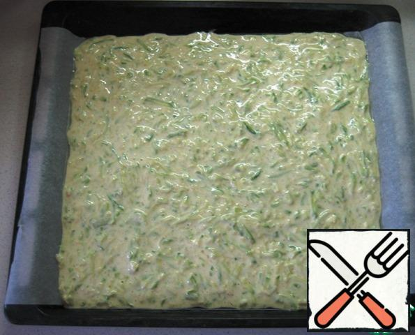 Cover the baking sheet with baking paper (my size is 29 x 33), grease with vegetable oil. Lay out the zucchini dough, evenly distributing it over the entire surface in an even layer.