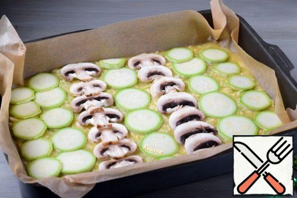Preheat the oven to 200-205°C. Cover the baking sheet (approximate size 25 X 35 cm) with baking parchment and put the zucchini mass. Level it out. Half of the zucchini cut into thin circles, mushrooms-thin slices. Arrange the pieces of zucchini and mushrooms on the surface of the zucchini mass in any order.
