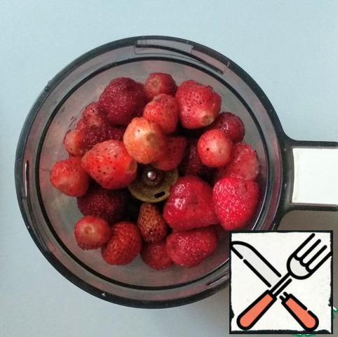 Wash the strawberries and put them in a blender.
