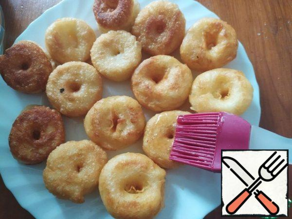 Ready-made doughnuts immediately transfer the skimmer to a previously prepared plate, cool, brush well impregnate the doughnuts with syrup.