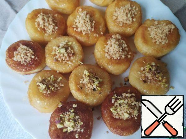 Chop the pistachios in any convenient way. Fill the holes in the doughnuts with crushed nuts.