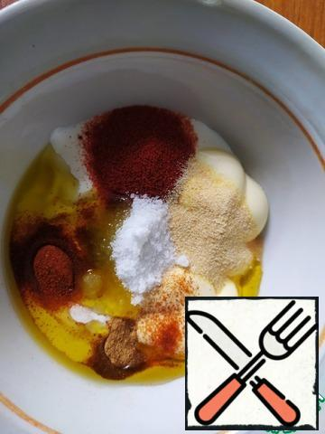For the marinade, mix olive oil, tomato sauce, sour cream and mayonnaise. Add salt and spices.