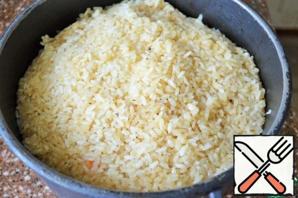 Cover with a lid and cook the pilaf over low heat for 20-25 minutes, until the liquid evaporates and the rice is ready.