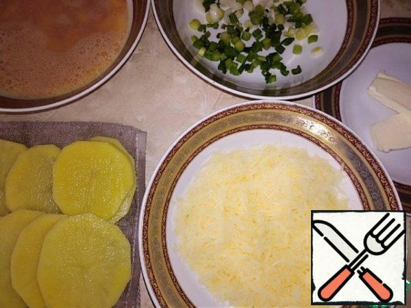 Ingredients for a hearty Breakfast are ready: egg filling: sliced thin slices, washed in cold water and dried with a napkin potatoes (do not keep long in the air); chopped green onions; grated on a medium grater hard cheese; 2 tablespoons of butter.