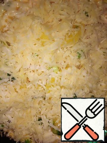 Close the lid and keep on low heat for 2 minutes. Use a knife to make gaps to allow the fill to flow down. Make sure that the bottom does not burn - add a little butter. Open the lid and spread the grated cheese on the surface.