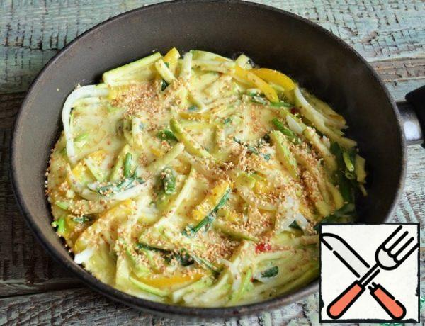 In a frying pan, heat 2 tbsp of oil, put the dough, distribute, sprinkle with sesame seeds. Fry for 3-4 minutes, medium heat.
