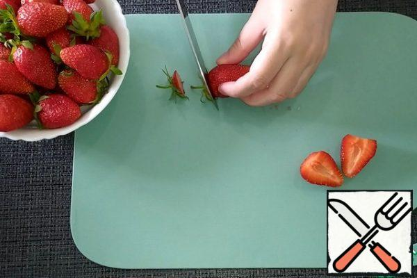 Wash the strawberries, dry them, and cut off the sepals. Part of berries cut in half, part of leave whole.
