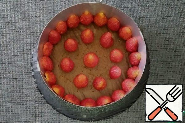 Ready to cool the sponge cake and put it in a split ring, the sides of which are previously lined with film. On the sponge cake in a circle, put the strawberry halves cut to the sides of the form, and in the middle - whole berries.