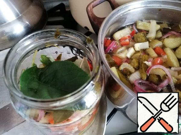 Remove the vegetables with a slotted spoon and arrange them in layers in the jars and lay the layers with currant and cherry leaves 1 PC. If desired, you can add one Bay leaf.