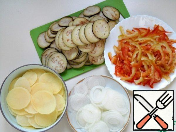 Onions, potatoes, eggplants to clean, wash, dry, cut into thin rings, bell peppers to wash, clean, divide into 4 parts and cut into thin strips.