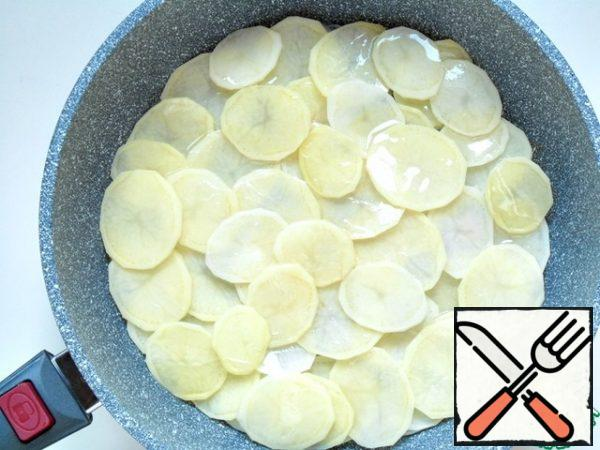 Mix the garlic and onion, spread evenly on the bottom of the pan, spread thin rings of potatoes on top, pour 3 tbsp of vegetable oil, cover with a lid, simmer over medium heat for 7-10 minutes.