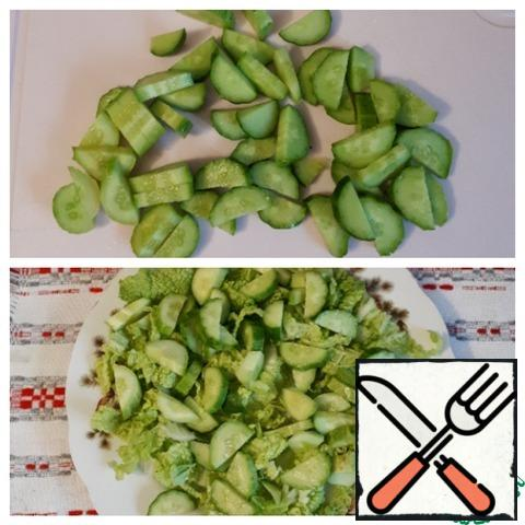 Cut fresh cucumbers into 5 mm thick slices and put them on a plate on the cabbage.