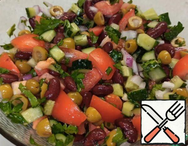 1. Cut the vegetables: cucumbers in cubes, tomatoes in medium slices, onions and herbs are crushed. Mix all the vegetables, add the canned beans (Canned beans must first be thrown into a colander to drain the liquid, and wash) and olives. 2. Salt, add oil and mix everything well.