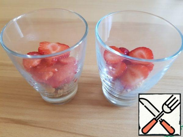 Put the crushed cookies in the cups. And sliced strawberries. ( one glass takes about 2 strawberries).