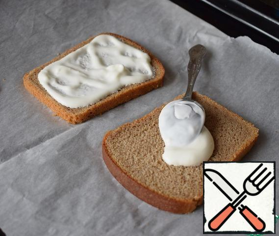 Spread sour cream on slices of bread.