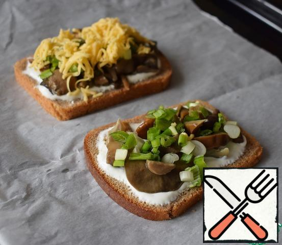 Put the green onions and cheese on the mushrooms.