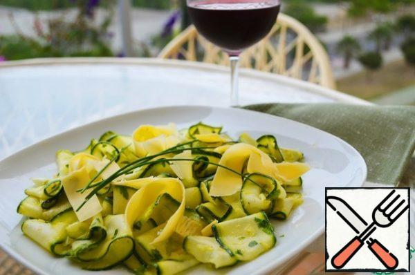 Spread the marinated zucchini on plates, sprinkle with Parmesan shavings and garnish with chives.