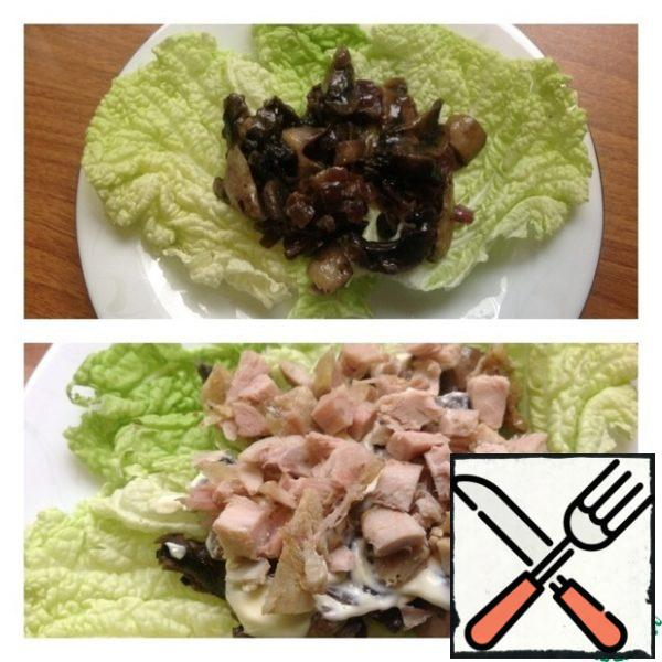 On a high heat in a frying pan in oil, fry the mushrooms cut into plates and finely chopped onions. A little salt and pepper. On the lettuce leaves, spread the cooled mushrooms with onions. Then a layer of mayonnaise or sour cream. Who likes it. Next, a layer of boiled chicken breast, cut into small cubes.