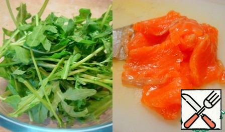 Wash the arugula, dry it and pick it in a large bowl with your hands. Cut the fish into thin plates.