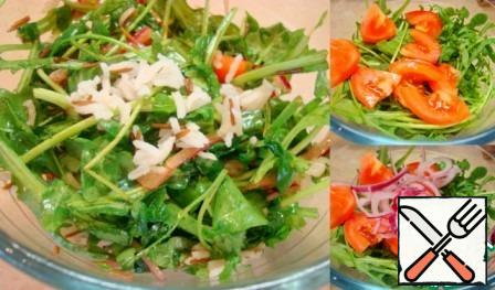 Mix the arugula, fresh and dried tomatoes, onions, fish and rice. Pour in the dressing, mix, put on a dish and sprinkle with feta cubes on top.