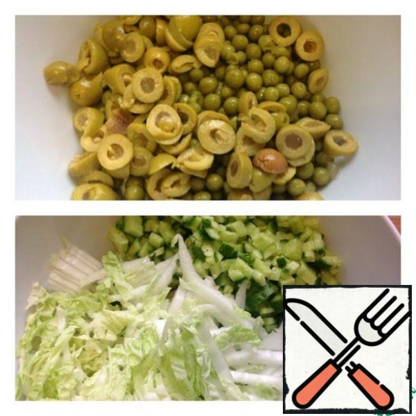 Drain the liquid from the peas and put 5 tbsp of Olives in a salad bowl. Cut the cucumber into small cubes and chop the cabbage.