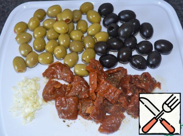 Peel and chop the garlic.  Leave the olives whole, but you can also cut them into rings.  Cut the tomatoes into 2-3 pieces.