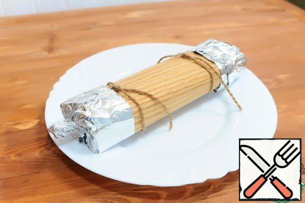 4. Wrap a sheet over the food, overlapping the edges at the top, and tie the roll with damp twine.  Foil the ends so that the melted cheese does not flow out of the roll.