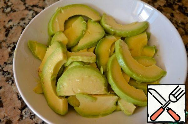 4. Peel the avocado, cut into slices of medium thickness and pour generously with lemon juice.